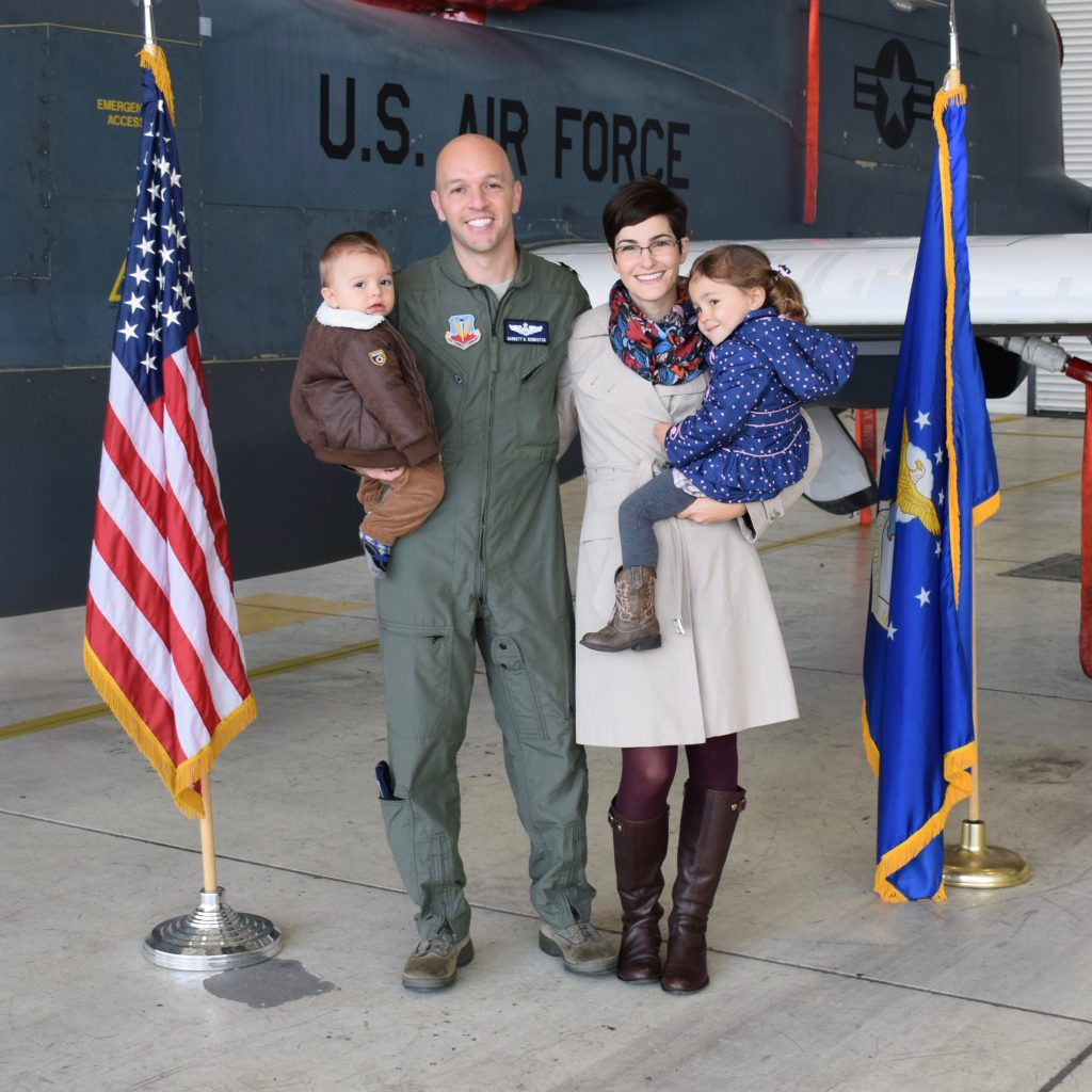 Monica stands with her US air force husband and 2 small children next to a plane